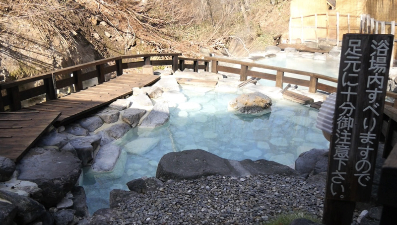 蔵王大露天風呂の露天風呂と足元注意の看板の写真