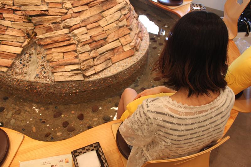 足湯カフェ「ほぐれすと」の足湯につかっている女性の写真