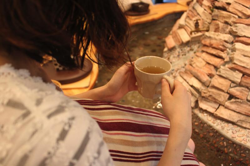 足湯カフェ「ほぐれすと」のジンジャーティーを飲む女性の写真