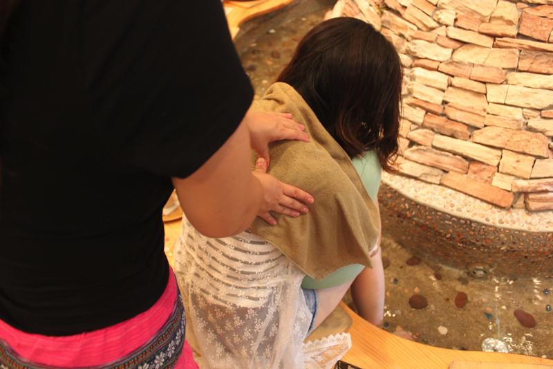 足湯カフェ「ほぐれすと」の湯もみを受けている女性の写真