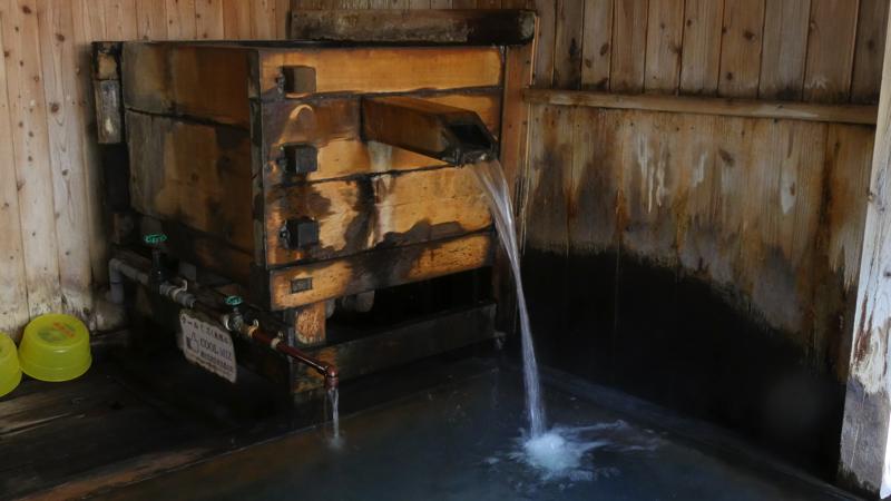 新高湯温泉の吾妻屋の湯溜めからお湯が注がれる様子の写真