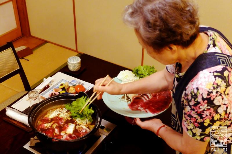 秘境温泉【油山苑】の牡丹鍋を調理する大女将の写真