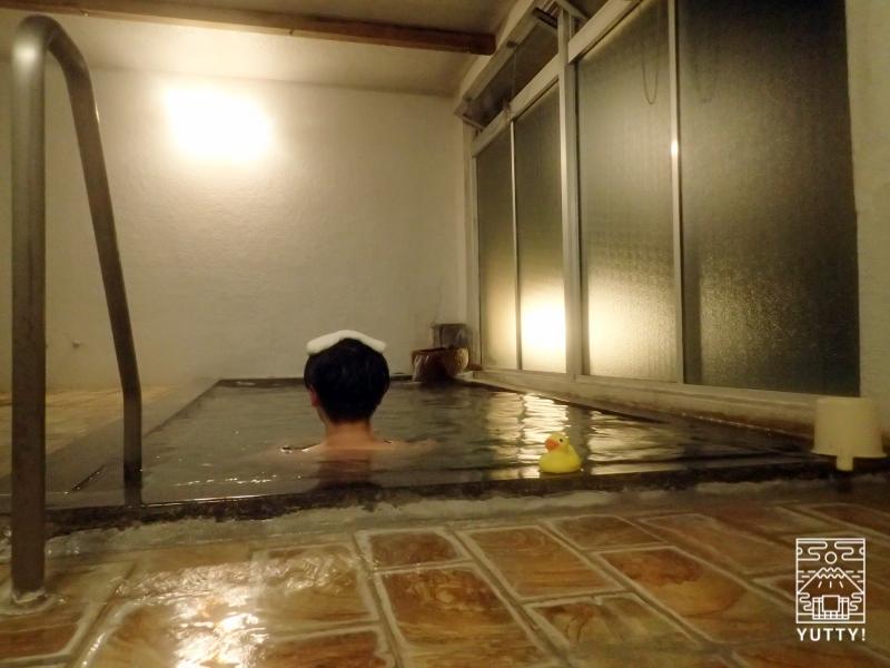 秘境温泉【油山苑】の内湯に浸かる男性とアヒルくんの写真