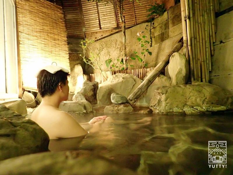 秘境温泉【油山苑】の露天風呂に浸かる男性の写真