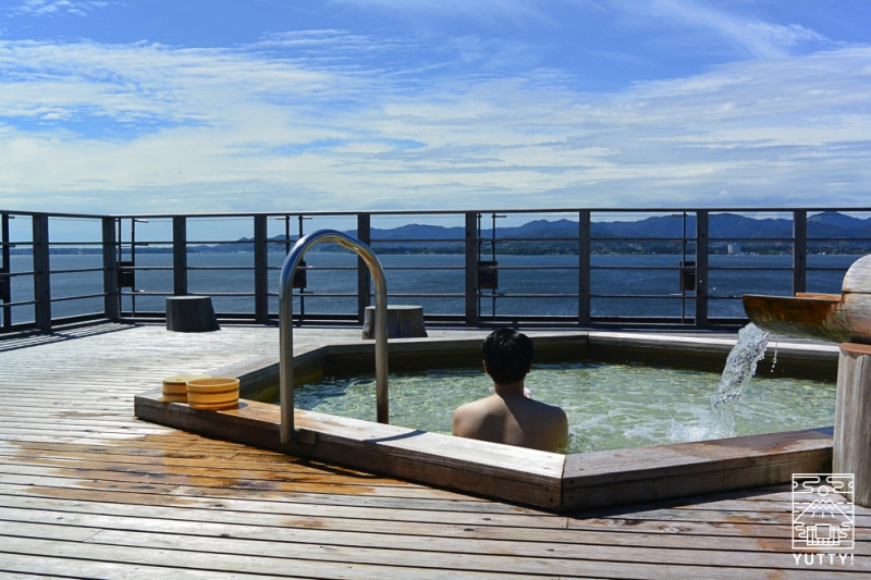 舘山寺サゴーロイヤルホテルの屋上の露天風呂「飛天」に浸かる男性の写真