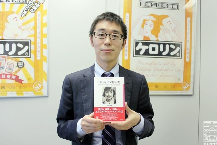 『幻の近代アイドル史』を手に持つ、代表取締役社長・笹山敬輔さんの写真
