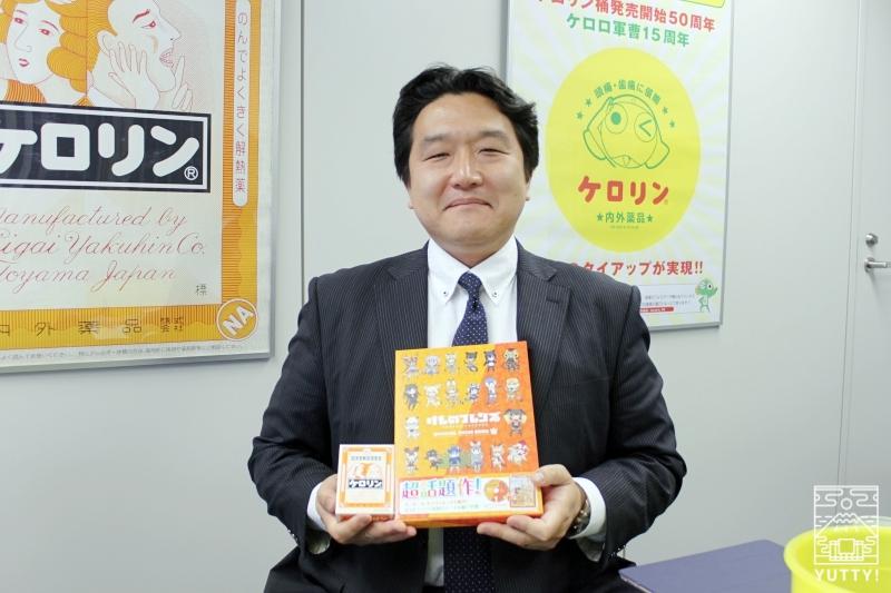 オフィシャルガイドブックとケロリンの箱を持った北村学さんの写真