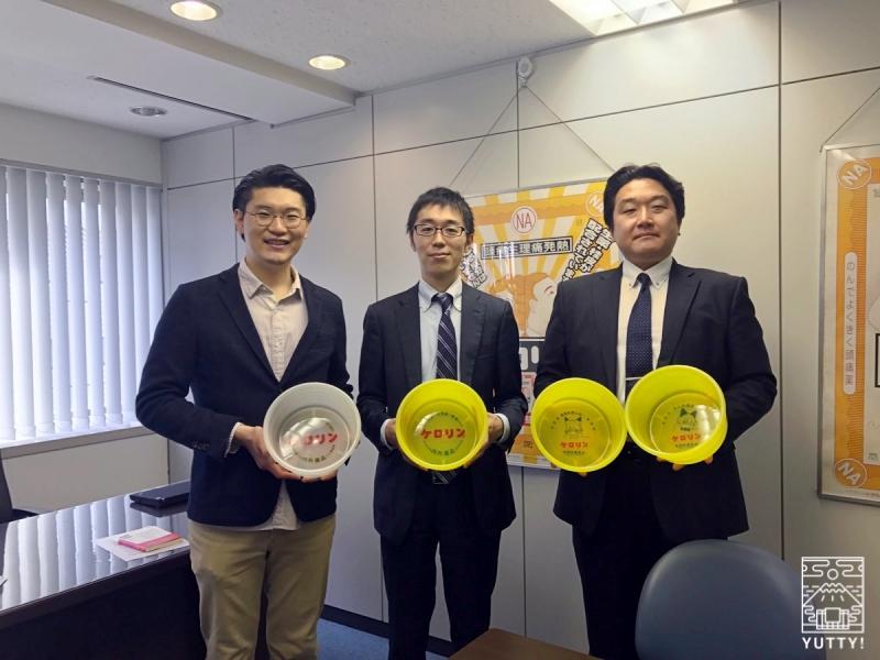 新旧ケロリン桶を持った、内外薬品の代表取締役社長・笹山敬輔さん、コラボ企画担当の北村学さんと、Yutty!編集長の写真