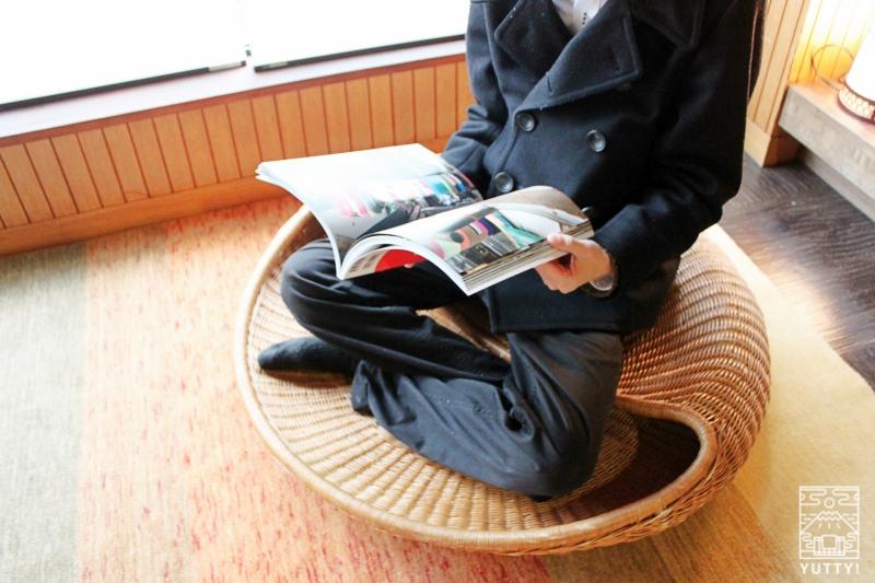 静岡天然温泉 おふろcafe bijinyu 美肌湯  の「あぐら座椅子」に座って雑誌を読んでいる写真