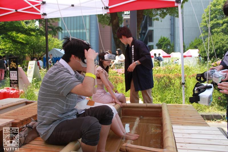 VRゴーグルをつけて足湯をしている男性の写真