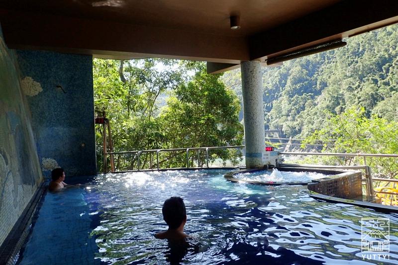 雄大な景色を眺めながら温泉につかる男性の写真